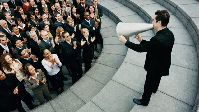 Businessman Standing on Steps Outside Talking Through a Megaphone, Large Group of Business People Listening and Applauding